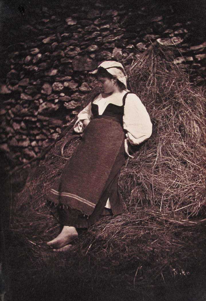 Girl leaning on pile of straw, with scythe